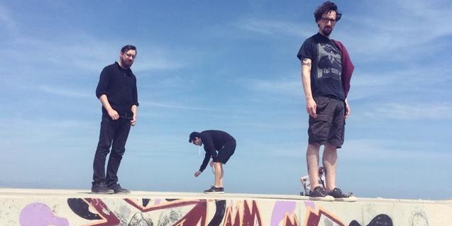 Els tres membres de la banda retratats pujats dalt d'un bloc de formigó ple de grafiti
