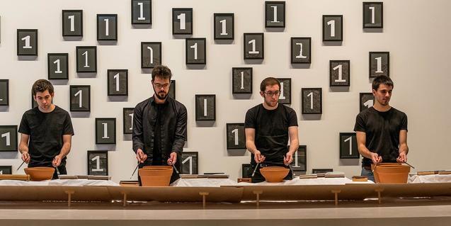 Cuatro integrantes de esta formación produciendo música con unos recipientes de cerámica