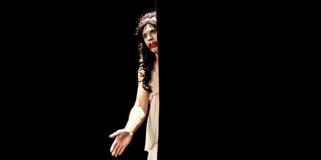 L'artista apareixent en la foscor des de darrera d'una porta en un moment de la representació
