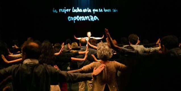 El públic amb els braços en creu seguint les indicacions del performer