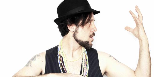 El músic sense camisa i vestint només una armilla i un barret negre