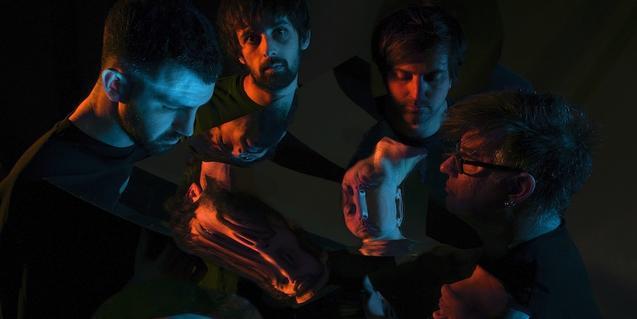 Els quatre components de la formació retratats en la foscor amb uns miralls que reflecteixen les seves imatges