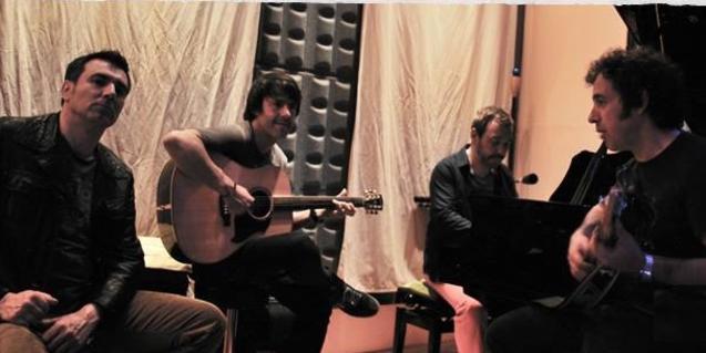 Los cuatro miembros de la banda ensayando en el estudio de grabación