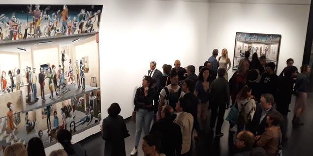 Un grupo de visitantes contempla uno de los cuadros durante la inauguración de la exposición