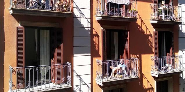 Veïns i veïnes als balcons de casa seva en una imatge copsada al barri Gòtic