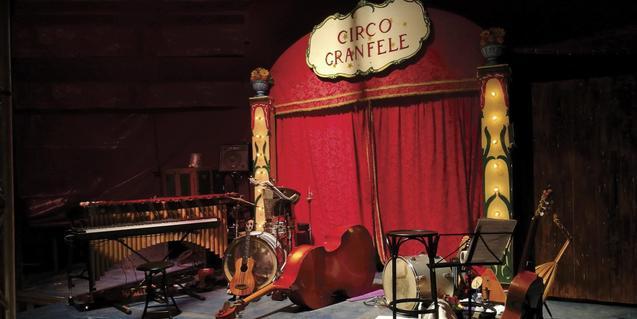 El teló d'un circ i un conjunt d'instruments abandonats al cartell de la gira d'enguany de la formació