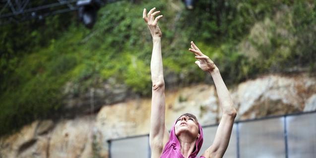 Una intèrpret aixeca el braç assenyalant cap al cel durant una representació al Teatre Grec de Montjuïc