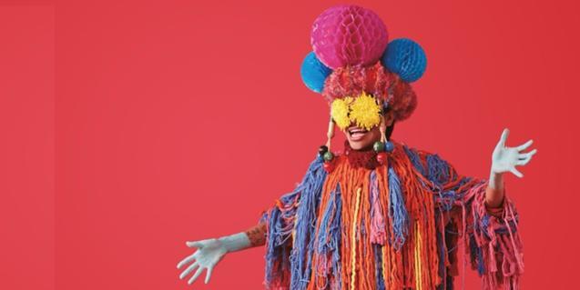 Un personaje vestido con un disfraz extravagante y de colores vivos en una de las imágenes de este año del festival