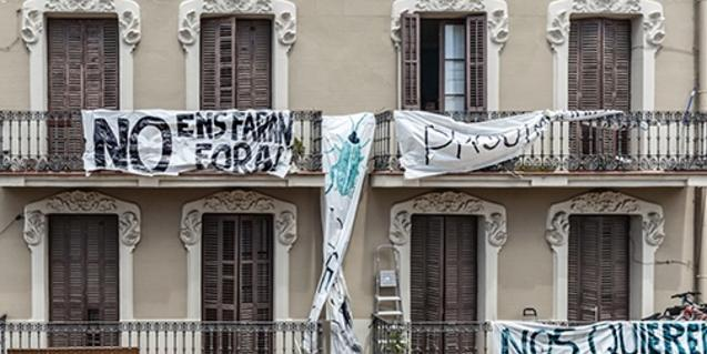 Fotografia d'un edifici amb pancartes penjades als balcons