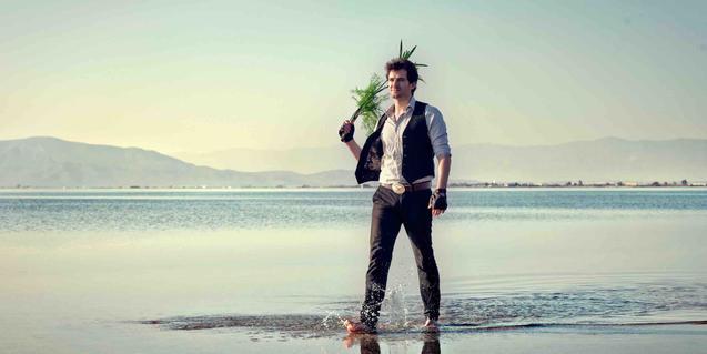 El cantautor retratado andando descalzo por la playa con el agua mojándole los pies
