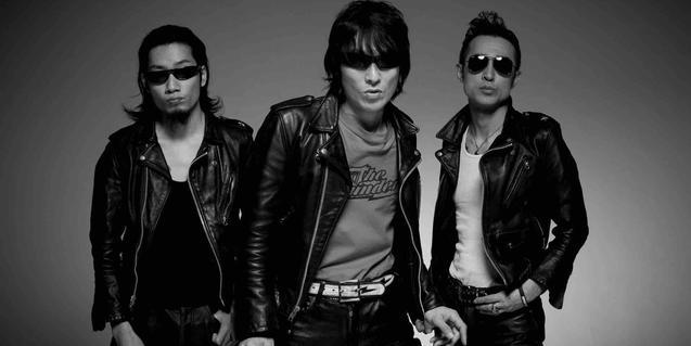 Retrato en blanco y negro de los tres integrantes de la banda con gafas de sol y chaquetas de cuero