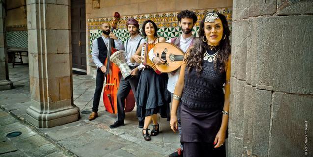 Els cinc membres del grup retratats amb els seus instruments al pati d'un edifici històric de Barcelona
