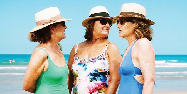 Tres mujeres en bañador con sombreros y gafas de sol retratadas en la playa