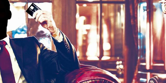 Un home amb el rostre cobert subjecta a la mà una tarja de crèdit