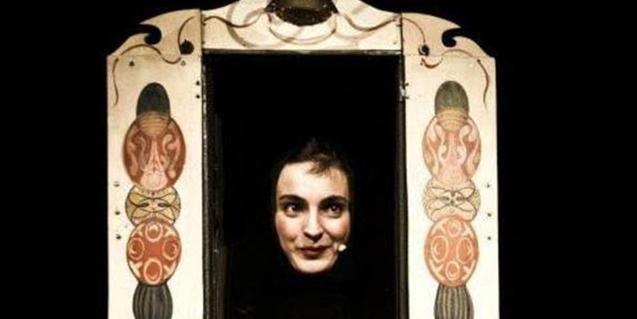 Fotografía del espectáculo, la artista y titiritera saca la cabeza en el pequeño escenario