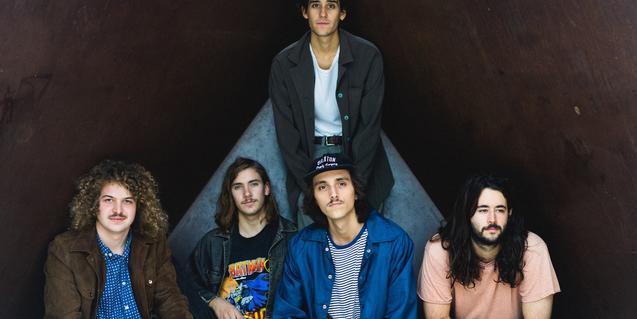 Los cinco integrantes de la banda retratados ante un fondo negro