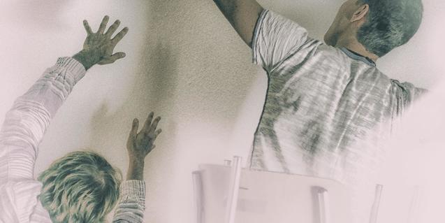 Dos intèrprets d'esquenes recolzen les mans sobre una paret blanca