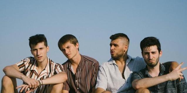 Els quatre joves integrants d'aquesta banda de pop retratats amb el cel de fons