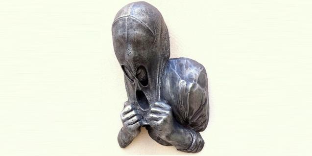 Una de las obras expuestas se una creación de un escultor que muestra un hombre intentando quitarse una máscara de la cabeza