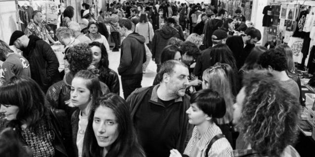 Una imagen en blanco y negro de una edición anterior de la feria discográfica con numerosos visitantes paseando entre los puestos de venta