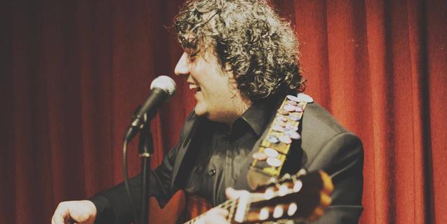 Retrato del músico Dimas Rodríguez cantando y tocando la guitarra