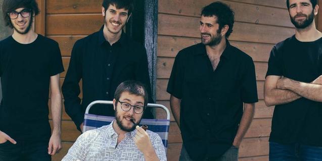 Retrato de grupo de la formación con el líder de la banda sentado y el resto de músicos en pie