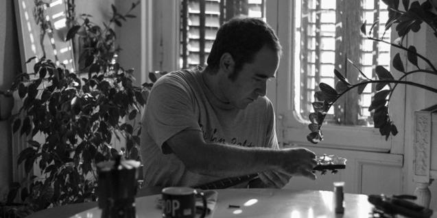 Retrato del músico afinando una guitarra ante una taza de café