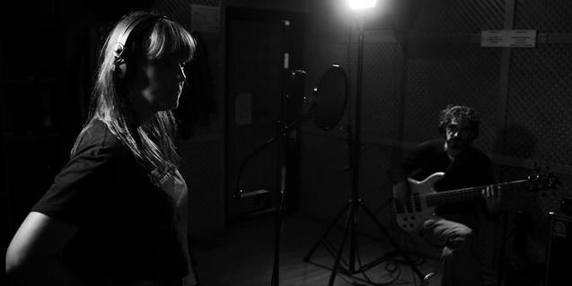 Retrato en blanco y negro de Izä y su guitarrista actuando en un espacio oscuro