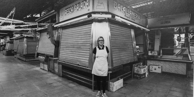 Una de les venedores del mercat retratada davant de la parada de bacallà de l'antic recinte
