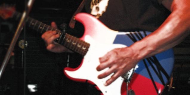Fotografía de la mano de un músico tocando una guitarra