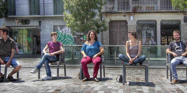 La artista Joana Gomila y sus músicos, sentados en unos bancos de la calle