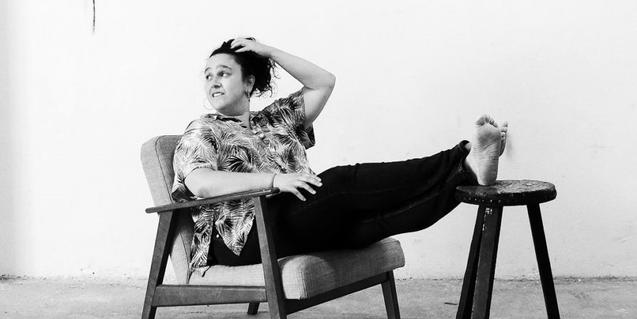 La artista retratada con los pies sobre una silla