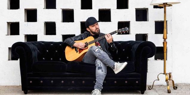 Retrato del músico sentado en un sofá y tocando la guitarra