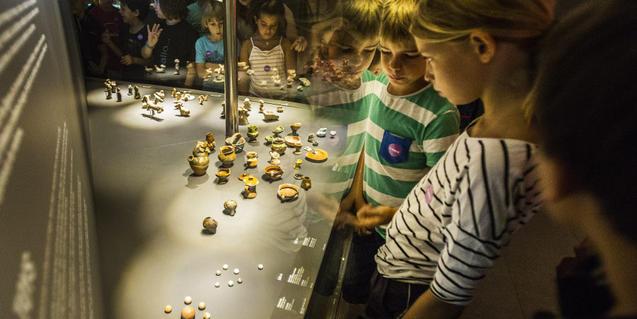 Fotografía de niños y niñas observando las piezas de una vitrina del museo del Born