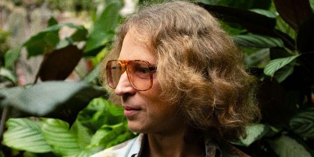 Retrato del músico australiano con unas grandes gafas y rodeado de plantas