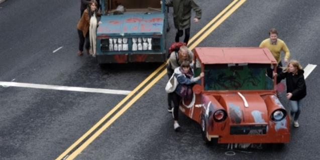 Imagen de unos ciudadanos empujando un coche en una calle