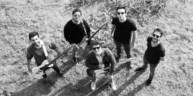 Els cinc membres de la banda retratats drets sobre la gespa en una vista zenital