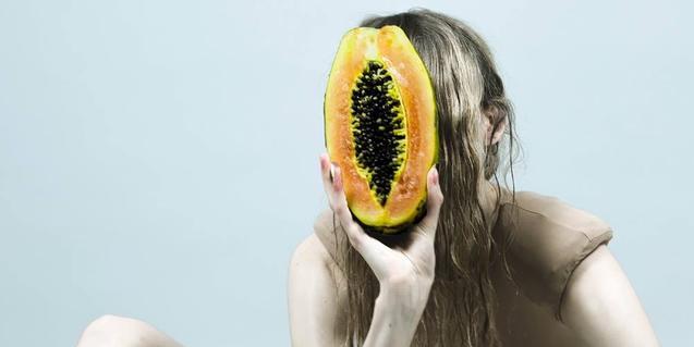 Una modelo retratada sosteniendo una fruta abierta ante su rostro