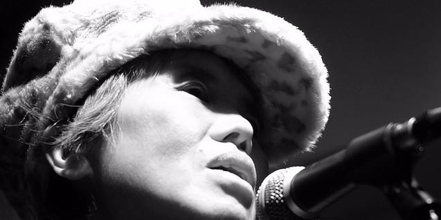 La intérprete y compositora japonesa cantando ante un micro con una gorra puesta
