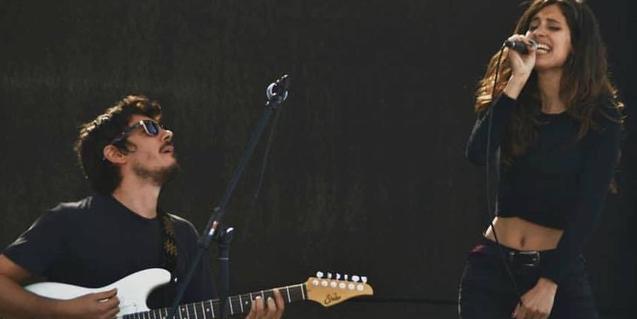 Retrat de la formació, amb Xavi Ricka tocant la guitarra i Eva Kaué cantant amb el micro a la mà