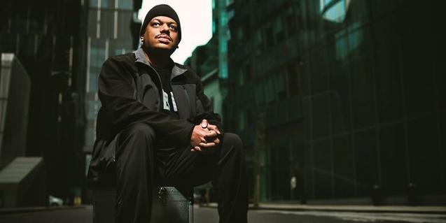 Retrato del productor de house y DJ sentado en la calle en una acera