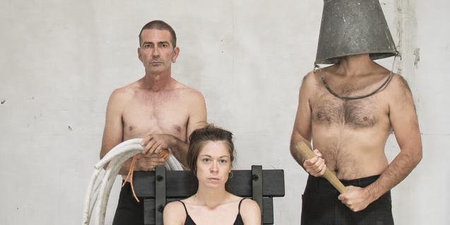Retrato de los protagonistas del espectáculo con una chica sentada en una silla y rodeada de dos hombres sin camisa uno de los cuales lleva un cubo en la cabeza que le cubre la cara