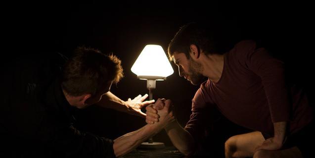 Els dos acròbates, fent un pols en un espai a les fosques, només il·luminat per una petita làmpada