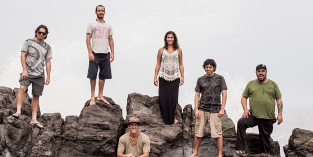 Els sis integrants de la banda retratats en unes roques a tocar del mar