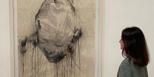 Una visitante retratada mientras contempla uno de los dibujos expuestos en la Galería Senda