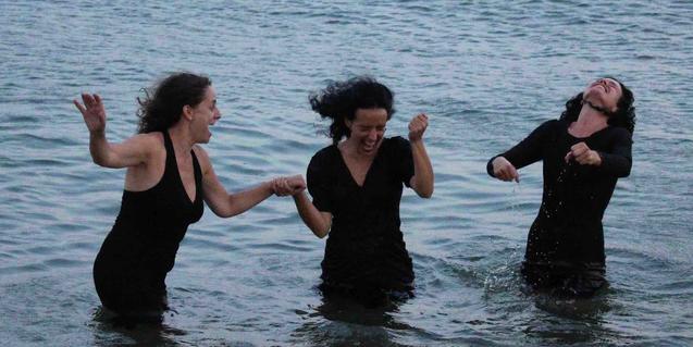 Las tres protagonistas en una playa con las piernas dentro del agua