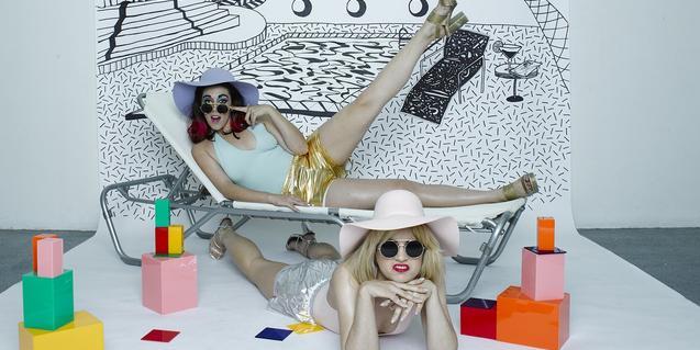 Las integrantes de este dúo, con gafas de sol y sombreros, ante un decorado que simula una piscina