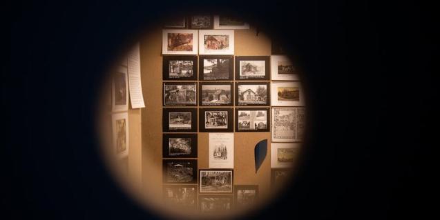 Una imagen de la muestra con una pared llena de fotografías colgadas vista a través de un agujero