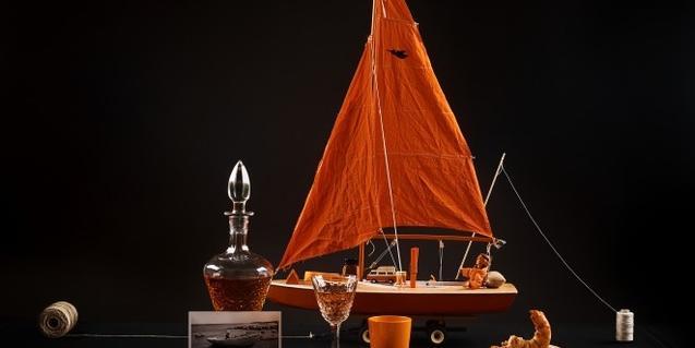 Un barco en miniatura con las velas de color naranja atraviesa una mesa dispuesta para comer