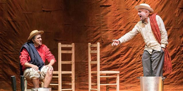 Los dos protagonistas de la función en el escenario llevando sombreros de paja y con los pies en un cubo